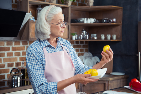 Senior woman in eyeglasses and apron looking at lemons in kitchen Фото со стока - 69495255