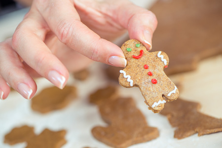Partial view on female hand holding cute gingerbread man cookie