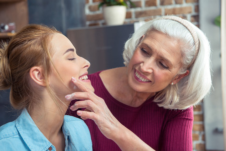 Happy grandmother removing flour from the cheek of her granddaughter