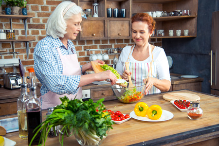 Smiling women in aprons cooking together in kitchen Stock Photo
