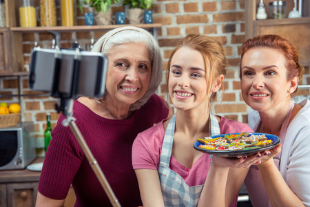 Family of three generations making selfie holding plate with Christmas cookies