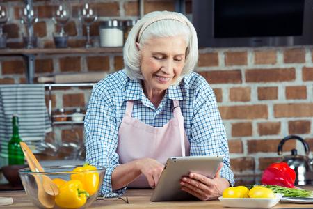 デジタル タブレットを使用して台所でエプロンで笑顔のシニア女性