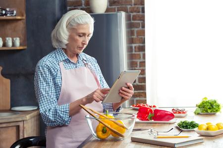 年配の女性が台所で野菜サラダを準備している間デジタル タブレットを使用して
