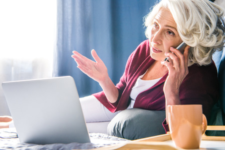 homeoffice: Attractive senior woman talking on smartphone while lying on bed