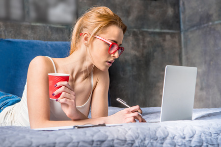 homeoffice: Attractive young woman in eyeglasses using laptop and holding paper cup on bed Stock Photo