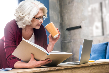 homeoffice: Attractive senior woman holding paper cup and reading book