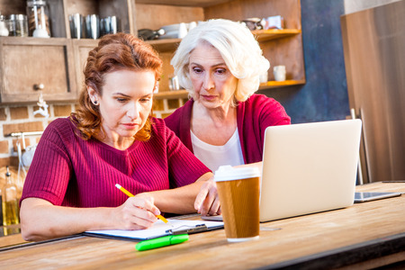 homeoffice: Mother and her adult daughter usind laptop and making notes sitting at table in kitchen