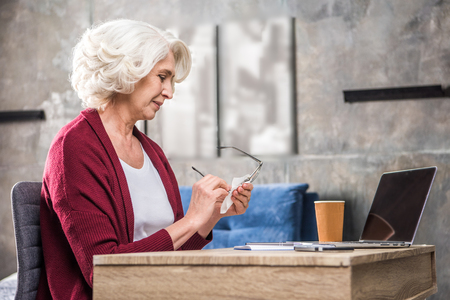 homeoffice: Smiling senior woman cleaning eyeglasses while sitting at desk with laptop