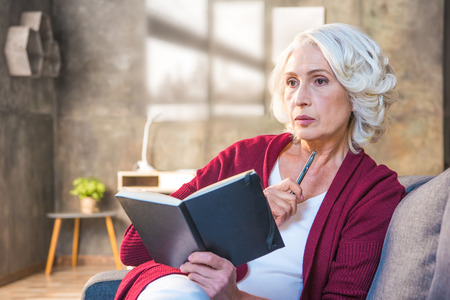 Senior woman sitting on sofa and making notes in notebook Stock Photo