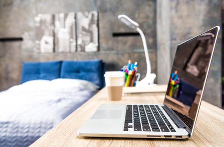 homeoffice: Close-up view of laptop on wooden table in bedroom