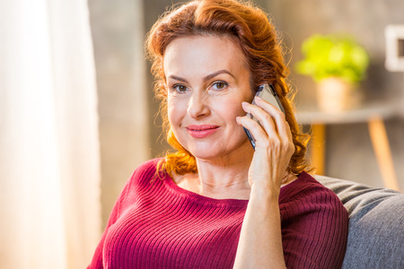Portrait of smiling woman talking on mobile phone and looking at camera Stock Photo
