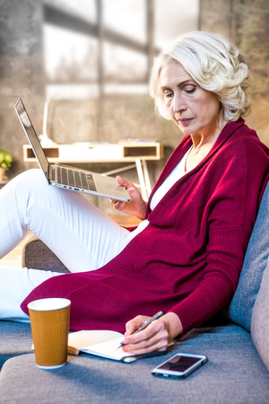 Senior woman using laptop sitting at sofa and making notes in notebook