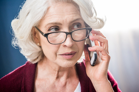 Attractive senior woman in eyeglasses talking on smartphone
