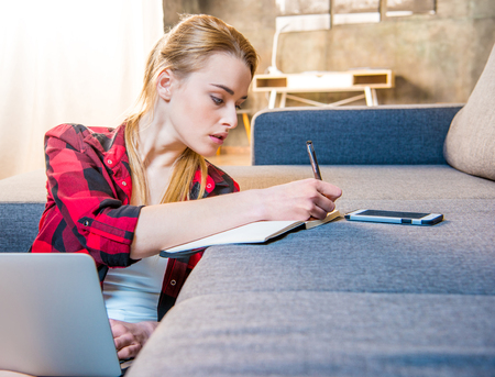 Teenage girl making notes in notebook while working on laptop Stock Photo