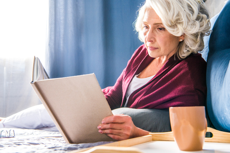 homeoffice: Attractive senior woman reading book while lying on bed