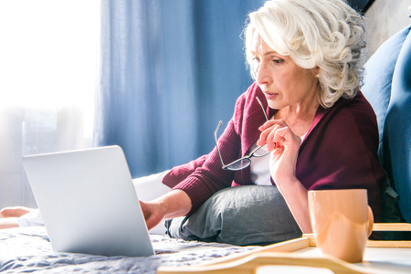 Attractive senior woman using laptop while lying on bed