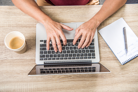 homeoffice: Top view of woman using laptop while sitting at desk Stock Photo