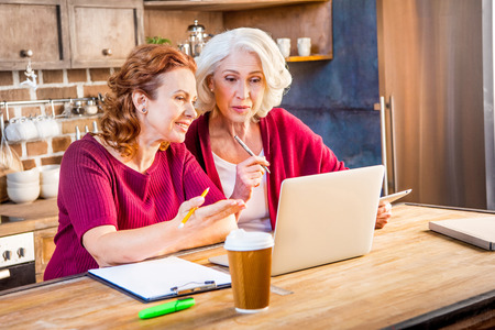homeoffice: Two women using laptop and making notes in kitchen Stock Photo