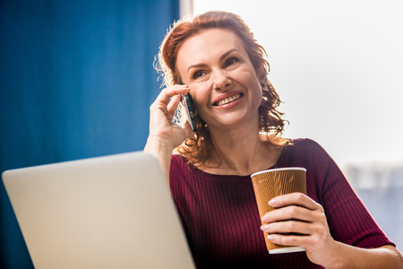 Smiling woman talking on smartphone and holding paper cup