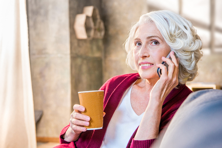 Portrait of senior woman talking on mobile phone and holding a cup of hot beverage