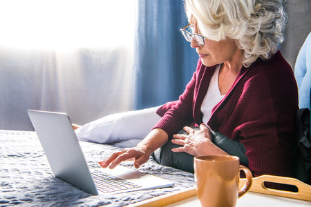 Attractive senior woman in eyeglasses using laptop while lying on bed