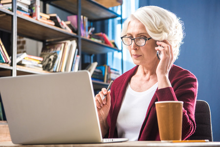 homeoffice: Attractive senior woman in eyeglasses using smartphone while sitting at desk with laptop and paper cup