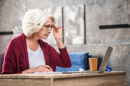 homeoffice: Senior woman adjusting eyeglasses while looking at laptop