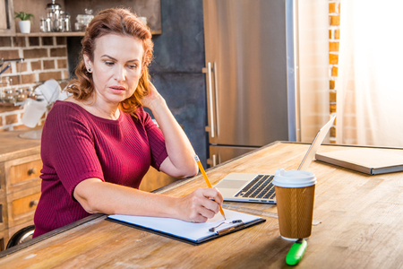 homeoffice: Woman making notes sitting in kitchen with laptop