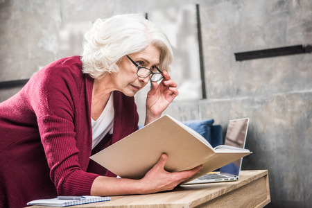 Attractive senior woman in eyeglasses reading book while sitting at desk with laptop