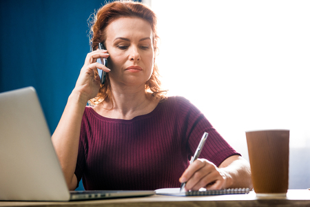 homeoffice: Attractive woman writing in notebook while talking on smartphone