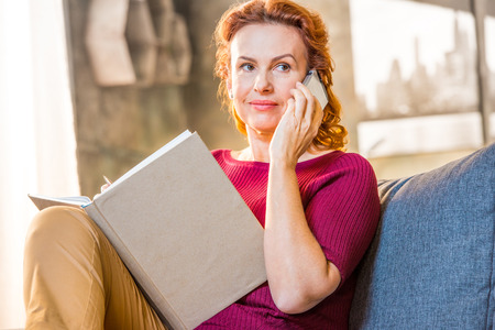 Woman talking on mobile phone sitting on sofa and holding a notebook