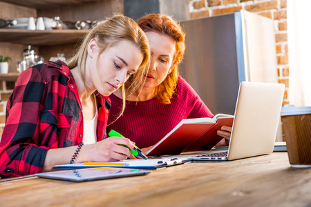 homeoffice: Woman and her teenage daughter usind laptop and making notes at home
