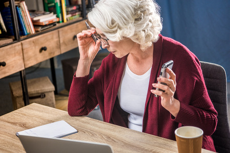 homeoffice: Attractive senior woman adjusting eyeglasses and holding smartphone