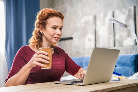 homeoffice: Attractive woman using laptop and holding paper cup Stock Photo