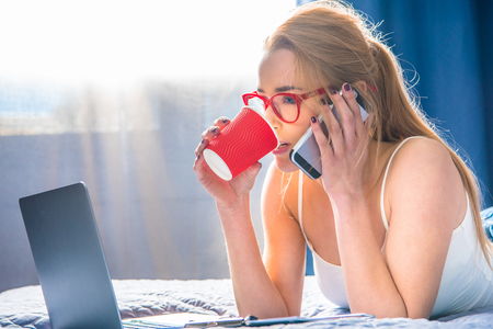 homeoffice: Teenage girl talking on smartphone and drinking coffee from paper cup