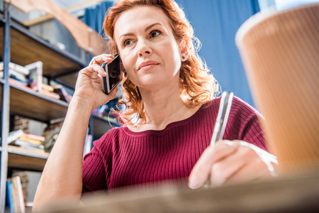 homeoffice: Attractive woman talking on smartphone and holding pen Stock Photo
