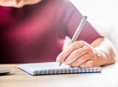commonplace: Close-up partial view of woman writing in notebook Stock Photo