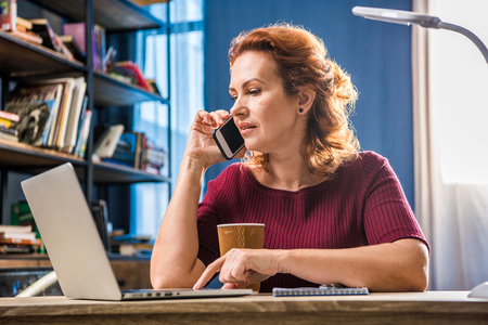 Attractive woman talking on smartphone while using laptop Stock Photo