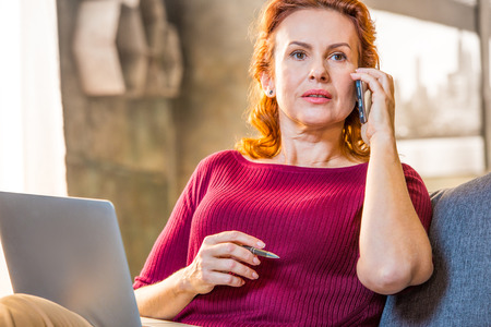 homeoffice: Woman talking on mobile phone sitting on sofa with laptop Stock Photo