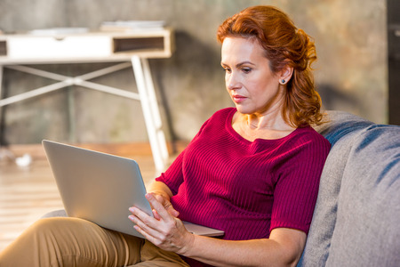 homeoffice: Woman using laptop sitting on sofa at home Stock Photo