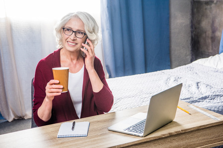 homeoffice: Attractive senior woman in eyeglasses talking on smartphone and holding paper cup