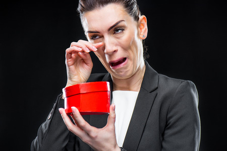 Crying businesswoman holding red toy heart on black