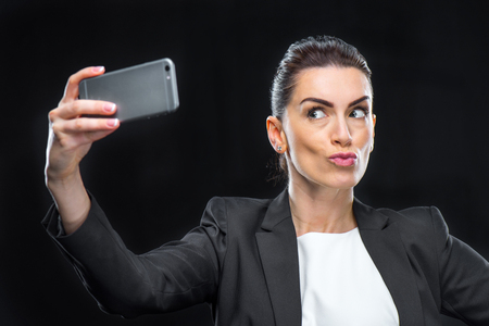 Businesswoman using smartphone and making duckface while taking selfie Stok Fotoğraf