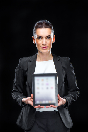 Attractive businesswoman showing digital tablet and smiling at camera
