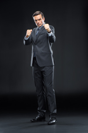 Handsome businessman in suit ready to boxing on black