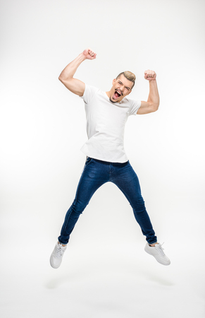 Full length portrait of exited young man jumping on white