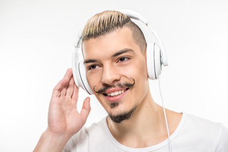 Happy stylish young man in headphones on white