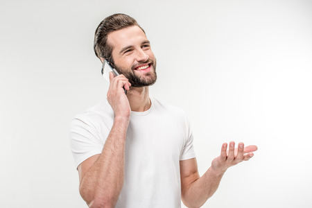Handsome smiling man in white t-shirt using smartphone