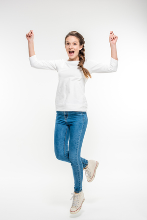 Exited young woman jumping on white