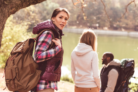 Group of young backpackers walking near river in autumn forest